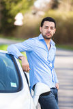 Latin american driver seated on the side of his new car Stock Photography