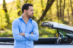 Latin american driver seated on the side of his new car Stock Image