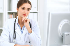 Latin american female doctor sitting at the table and working by computer at hospital office. The physician or therapist. Makes a diagnosis. Health care Royalty Free Stock Photography