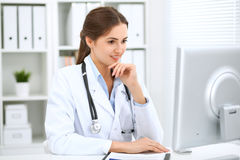 Latin american female doctor sitting at the table and working by computer at hospital office. The physician or therapist royalty free stock image