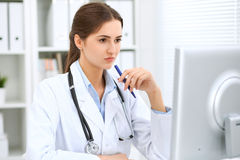 Latin american female doctor sitting at the table and working by computer at hospital office. The physician or therapist. Makes a diagnosis. Health care Stock Image
