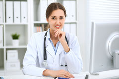 Latin american female doctor sitting at the table and working by computer at hospital office. The physician or therapist. Makes a diagnosis. Health care Stock Photo