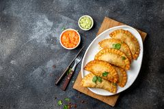 Latin American fried empanadas with tomato and avocado sauces. Top view.  stock images