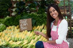 Latin american saleswoman at farmers market with corn and vegetables. Latin american saleswoman outdoors at latin american farmers market with corn and royalty free stock photos