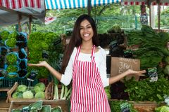 Latin american woman presenting vegetables and salad at farmers. Latin american woman presenting vegetables and salad outdoors at farmers market royalty free stock images