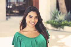 Latin american young adult woman in green shirt royalty free stock photography