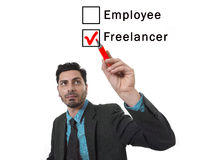 Latin attractive businessman choosing freelancer to employee option at work formular ticking box with red marker Royalty Free Stock Image