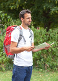Latin backpacker with map. Smiling backpacker from South America looking for the right way stock images