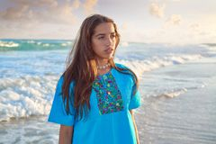 Latin beautiful girl in Caribbean beach sunset. With embroidery dress Stock Photo