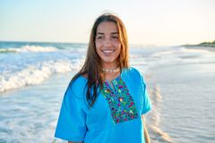 Latin beautiful girl in Caribbean beach sunset. With embroidery dress Stock Photos