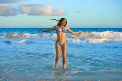 Latin bikini girl jumping in Caribbean beach. Latin beautiful bikini girl happy jumping in Caribbean beach sunset Royalty Free Stock Image