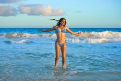 Latin bikini girl jumping in Caribbean beach. Latin beautiful bikini girl happy jumping in Caribbean beach sunset Stock Photo
