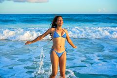 Latin bikini girl jumping in Caribbean beach. Latin beautiful bikini girl happy jumping in Caribbean beach sunset Stock Images