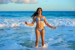 Latin bikini girl jumping in Caribbean beach. Latin beautiful bikini girl happy jumping in Caribbean beach sunset Royalty Free Stock Photos