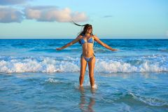 Latin bikini girl jumping in Caribbean beach. Latin beautiful bikini girl happy jumping in Caribbean beach sunset Stock Photos