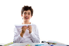 Latin boy playing with a paper airplane sitting in front of home Stock Photography