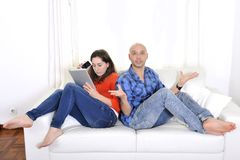 Latin boyfriend frustrated , upset and mad at girlfriend busy on tablet Stock Images