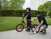 Latin Boys Adjusting a Kid's Bike Royalty Free Stock Image