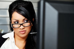 Latin business woman consultant. Hispanic female with black hair and glasses behind monitor Stock Image