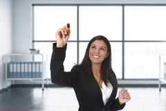 Latin business woman in formal suit writing with marker on invisible virtual screen or board at modern office. Young attractive latin business woman in formal royalty free stock images