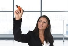Latin business woman in formal suit writing with marker on invisible virtual screen or board at modern office Stock Photos