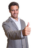 Latin businessman in grey suit showing thumb up Stock Images