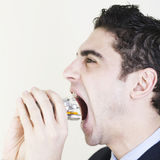 Hispanic businessman eating pills. Latin businessman puting medicine in his mouth in a aggresive way stock images
