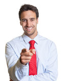Latin businessman with red tie pointing at camera Royalty Free Stock Photos
