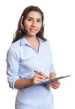 Latin businesswoman with headset and clipboard Stock Photo