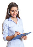 Latin businesswoman with headset writing notes Stock Photo