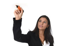 Latin businesswoman in office suit writing with marker on invisible virtual screen or board Stock Photo