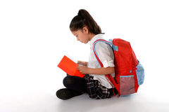 Latin child reading textbook or notepad smiling sitting on the floor Stock Photo