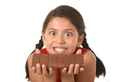 Latin child in red dress holding with both hands big chocolate bar in front of her crazy excited face expression Royalty Free Stock Photo