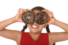 Latin child in red dress playing with donuts in her hands putting them on her face as cake eyes Royalty Free Stock Photo