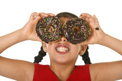 Latin child in red dress playing with donuts in her hands putting them on her face as cake eyes Stock Photography