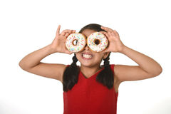 Latin child in red dress playing with donuts in her hands putting them on her face as cake eyes Royalty Free Stock Photos