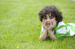 Latin Child Relaxing in the Grass Royalty Free Stock Photography