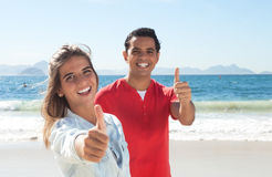 Latin couple at beach showing thumb up Stock Photography