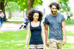 Latin Couple walking holding hands over meadow stock photography