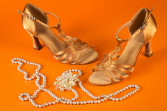 Latin dance shoes. With pearls accessories on orange background Stock Photo