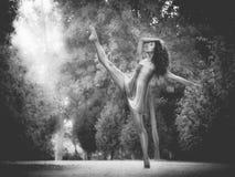 Latin dancer with leg raised in road full of vegetation monochro. Latin dancer with leg raised at sunset in park monochrome Stock Photo