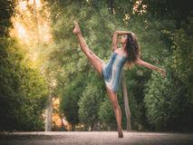 Latin dancer with leg raised in road full of vegetation. Latin dancer with leg raised at sunset in park Royalty Free Stock Photos