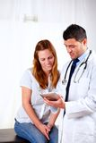 Latin doctor and a female looking to tablet PC Royalty Free Stock Images