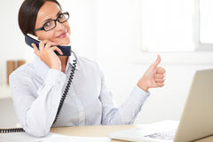 Latin employee happily doing customer service. Latin employee with spectacles happily doing customer service in the company office Royalty Free Stock Images