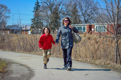 Mother Guiding Her Child. Hispanic family walking through path with joy. Latin family composed of a mother and her child walking through a path with joy and Stock Image