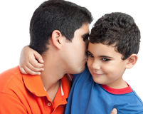 Latin father kissing his beautiful son. Isolated on a white background royalty free stock image