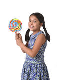 Latin female child holding huge lollipop happy and excited in cute blue dress and pony tails candy concept Stock Photo
