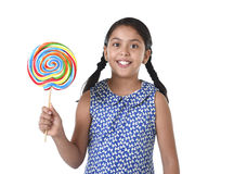 Latin female child holding huge lollipop happy and excited in cute blue dress and pony tails candy concept Royalty Free Stock Photos