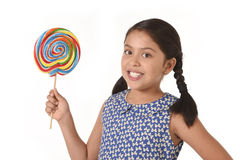 Latin female child holding huge lollipop happy and excited in cute blue dress and pony tails candy concept Royalty Free Stock Photo