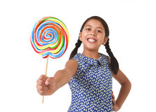 Latin female child holding huge lollipop happy and excited in cute blue dress and pony tails candy concept Stock Image